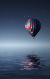 Hot Air Balloon reflected over still Night ocean